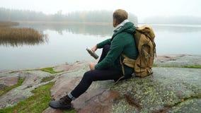 Un hombre de mediana edad con la mochila que se sienta en una orilla rocosa del mar Báltico metrajes