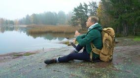 Un hombre de mediana edad con la mochila que se sienta en una orilla rocosa del mar Báltico almacen de video