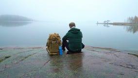 Un hombre de mediana edad con la mochila que se sienta en una orilla rocosa del mar Báltico almacen de metraje de vídeo