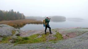 Un hombre de mediana edad con una mochila que fotografía fauna en una orilla rocosa metrajes