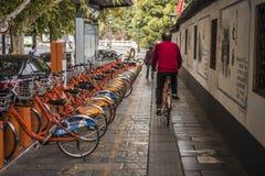Un hombre de mediana edad en una camisa roja monta una bicicleta compartida a través de un aparcamiento compartido de la biciclet