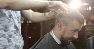 Un hombre de mediana edad que habla y que sonríe en barbería metrajes