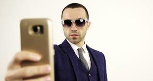 Un hombre de moda joven hace un selfie en un teléfono móvil almacen de video