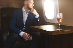 Un hombre de negocios acertado joven en un traje costoso se sienta en la silla de un jet privado con un vidrio de champ?n en el s fotos de archivo libres de regalías