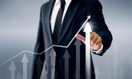 Un hombre de negocios acertado, manos toca el gráfico que representa subidas del beneficio encendido mucho más fotografía de archivo libre de regalías