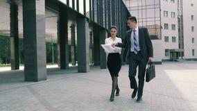Un hombre de negocios acertado y su ayudante que caminan al centro de negocios que discute los planes metrajes