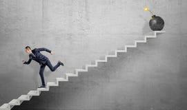 Un hombre de negocios asustado que corre abajo de las escaleras concretas grises lejos de una bomba grande del hierro con un fusi Fotos de archivo libres de regalías
