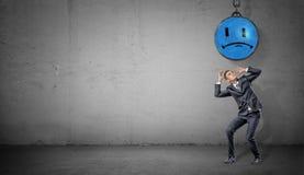Un hombre de negocios asustado se coloca en fondo concreto debajo de una bola arruinadora con una cara triste azul pintada Foto de archivo libre de regalías