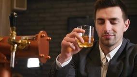 Un hombre de negocios bebe el whisky en una barra almacen de video