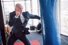Un hombre de negocios calvo enojado bate una pera del boxeo en el gimnasio Concepto de gestión de la cólera fotografía de archivo