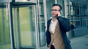Un hombre de negocios camina en una calle, haciendo una llamada, cierre para arriba
