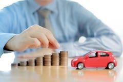 Un hombre de negocios un coche del juguete y una pila de monedas Imagen de archivo