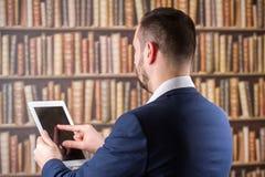 Un hombre de negocios coloca con la suya la parte posterior y trabaja en una tableta en Imagen de archivo