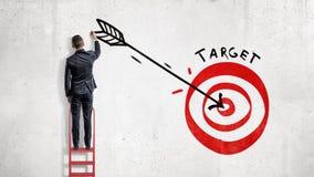 Un hombre de negocios coloca y dibuja en la pared una flecha grande en el centro de una blanco roja del tiro al arco imagenes de archivo