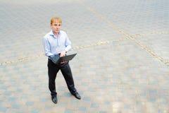 Un hombre de negocios con su computadora portátil Imágenes de archivo libres de regalías