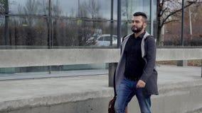 Un hombre de negocios con una cartera, caminando a través de la ciudad Un hombre camina abajo de la calle en negocio almacen de video