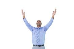 Un hombre de negocios concentrado con los brazos para arriba Imagen de archivo libre de regalías
