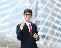Un hombre de negocios enérgico muy feliz con sus brazos aumentados foto de archivo