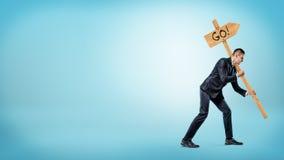 Un hombre de negocios en el fondo azul que lleva a cabo una señal de tráfico pesada con un ` va escritura del ` en ella Foto de archivo