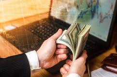Un hombre de negocios en un traje cuenta dólares en una tabla Imágenes de archivo libres de regalías