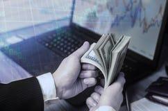 Un hombre de negocios en un traje cuenta dólares en una tabla en las manos o Fotografía de archivo libre de regalías