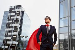 Un hombre de negocios en un traje del super héroe se opone a un b constructivo Imagen de archivo