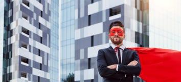 Un hombre de negocios en un traje del super héroe se opone a un negocio b Fotografía de archivo libre de regalías