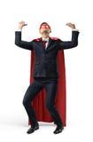 Un hombre de negocios en traje del super héroe sobre su traje que intenta llevar a cabo un objeto pesado invisible pesado desde a Fotografía de archivo