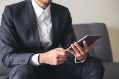 Un hombre de negocios en un traje gris que se sienta en la tenencia del sofá, usando y mirando la PC de la tableta para el trabaj Imágenes de archivo libres de regalías