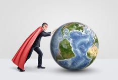Un hombre de negocios en un cabo rojo del super héroe que empuja y que rueda un globo grande en el fondo blanco Imagenes de archivo
