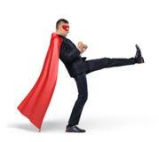 Un hombre de negocios en un cabo rojo del super héroe que golpea un objeto con el pie invisible en el fondo blanco Foto de archivo libre de regalías