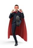 Un hombre de negocios en un cabo rojo del super héroe que golpea un objeto con el pie invisible en el fondo blanco Foto de archivo