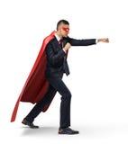 Un hombre de negocios en un cabo rojo del super héroe y una máscara que se colocan en vista lateral en la posición de sacador res Fotos de archivo libres de regalías