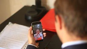 Un hombre de negocios en un traje, sentándose en la oficina en su escritorio, lleva a cabo una charla video con una muchacha en l almacen de video