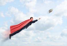 Un hombre de negocios en un vuelo del cabo del super héroe en el cielo que intenta coger un billete de banco de 100 USD Imagenes de archivo