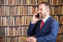 Un hombre de negocios en una chaqueta azul y el lazo rojo hablan al teléfono con g Foto de archivo