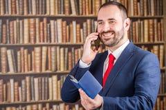 Un hombre de negocios en una chaqueta azul y el lazo rojo hablan al teléfono con p Imágenes de archivo libres de regalías