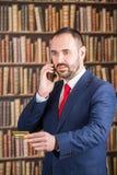Un hombre de negocios en una chaqueta azul y un lazo rojo dicta por el teléfono Foto de archivo