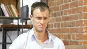 Un hombre de negocios enojado y desesperado infeliz triste joven en su oficina creativa almacen de metraje de vídeo