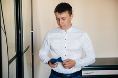 Un hombre de negocios está considerando sus accesorios para un vestido de boda El individuo pone un traje y consulta con el amigo Imágenes de archivo libres de regalías