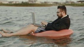 Un hombre de negocios está trabajando detrás de un ordenador portátil que se sacude en las ondas de un depósito mientras que sien almacen de video