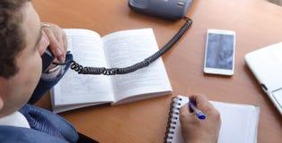 Un hombre de negocios habla en un teléfono de la línea horizonte y hace notas Fotos de archivo libres de regalías