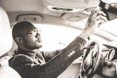 Un hombre de negocios joven en un traje que se sienta detr?s de la rueda de un coche costoso ajusta un espejo de la vista posteri imágenes de archivo libres de regalías