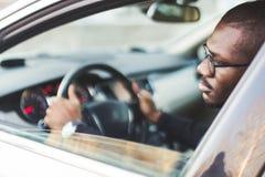 Un hombre de negocios joven en un traje se sienta en la rueda de un coche costoso imagen de archivo