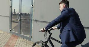 Un hombre de negocios joven en un traje de moda se sienta en una bicicleta y monta alrededor de la ciudad metrajes