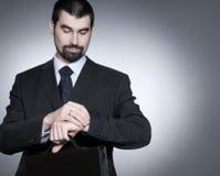 Un hombre de negocios joven está controlando el tiempo Fotos de archivo libres de regalías