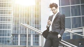 Un hombre de negocios joven está enrollando el teléfono imagenes de archivo
