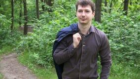 Un hombre de negocios joven pasa a través del bosque en un día soleado almacen de video