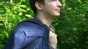 Un hombre de negocios joven pasa a través del bosque en un día soleado almacen de metraje de vídeo