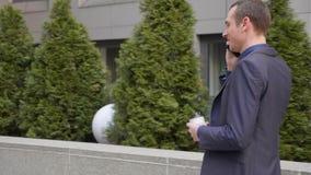 Un hombre de negocios joven que camina abajo de la calle y comunica feliz en la llamada de teléfono